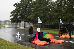 Farnborough, UK. 2nd October, 2021. Extinction Rebellion climate activists lie in the road locked to fuel barrels to block an entrance to Farnborough Airport. Activists blocked three entrances to the private airport to highlight elevated carbon dioxide levels produced by super-rich passengers using private jets and 'greenwashing' by the airport in announcing a switch to sustainable aviation fuel (SAF).