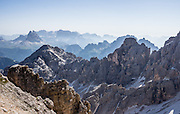 """From Rifugio Guido Lorenzi on Monte Cristallo in the Ampezzo Dolomites, look northeast across blue ridges of the Sesto Dolomites (Dolomiti di Sesto, or Sexten/Sextner/Sextener Dolomiten) to the pyramids of Tre Cime di Lavaredo (Italian for """"Three Peaks of Lavaredo,"""" called Drei Zinnen or """"Three Merlons"""" in German). A lift to Forcella Staunies on Monte Cristallo gives unforgettable views over the Dolomites mountains (part of the Southern Limestone Alps) near Cortina d'Ampezzo, in the Province of Belluno, Veneto region, Italy, Europe. Monte Cristallo lies within Parco Naturale delle Dolomiti d'Ampezzo. Directions: From Cortina, drive 6km east on SR48 to the large parking lot for Ski Area Faloria Cristallo Mietres (just west of Passo Tre Croci Federavecchia). Take a chair-lift from Rio Gere to Son Forca (rising from 1698m to 2215m). Then take the old style ovovia (egg-shaped) Gondellift Forcella Staunies to Rifugio Guido Lorenzi (2932m) for astounding views. Climbers enjoy spectacular via ferrata routes here. Cortina gained worldwide fame after hosting the 1956 Winter Olympics. UNESCO honored the Dolomites as a natural World Heritage Site in 2009."""