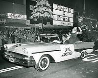 1957 Jayne Mansfield sits on the back of a convertible during the Santa Claus Lane Parade