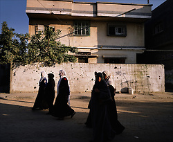 Women are seen outside a home marked with shrapnel from Israeli artillery fire, Beit Hanoun, Gaza Strip, Palestinian Territories, Nov. 24, 2006. According to Human Rights Watch, since September 2005, Israel has fired about 15,000 rounds at Gaza while Palestinian militants have fired around 1,700 back.