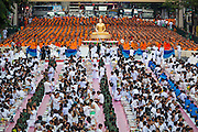 08 SEPTEMBER 2013 - BANGKOK, THAILAND: People and Buddhist monks pray during a mass alms giving ceremony in Bangkok. 10,000 Buddhist monks participated in a mass alms giving ceremony on Rajadamri Road in front of Central World shopping mall in Bangkok. The alms giving was to benefit disaster victims in Thailand and assist Buddhist temples in the insurgency wracked southern provinces of Thailand.       PHOTO BY JACK KURTZ