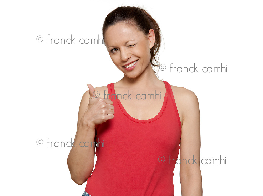 Portrait of cute expressive woman winking and gesturing thumbs up in studio on isolated white background
