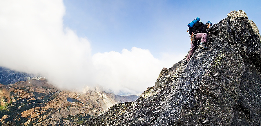 Climber Obadiah Reid scrambles up the West Ridge of Mount Stuart, Alpine Lakes Wilderness, Washington on September 6, 2008. Ingalls Lake is visible in the valley below.