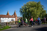 An electric cycling tour group stop to admire a traditional Oast house near Staplehurst, Kent, England, UK. Oast Houses are iconic in Kent and Surrey as they were used to store hops.