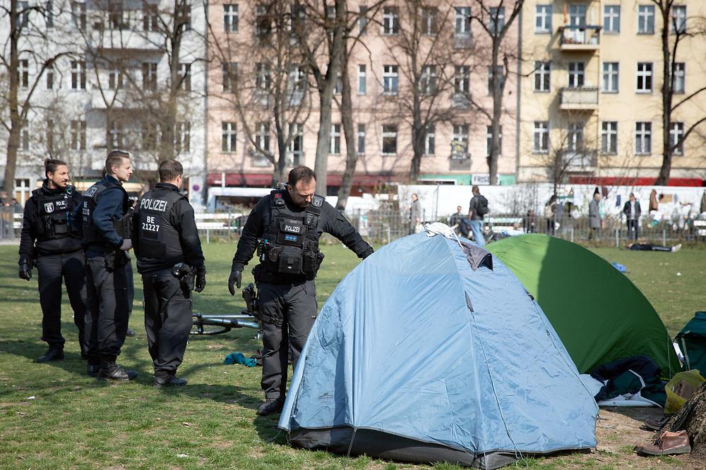 Polizisten weisen campierende Wohnungslose am Boxhagener Platz in Berlin Friedrichshain auf die Ausgansbeschränungen und das Kontaktverbot hin, wonach gemäß der Verordnung zur Eindämmung der COVID-19 - Pandemie (Coronavirus SARS-CoV-2) längerens Verweilen in der Öffentlichkeit verboten ist. Seit dem 23.02.2020 gilt in Berlin ein Kontakverbot und eine Ausgangsbeschränkung, um die Ausbreitung des Coronavirus zu bekämpfen. <br /> <br /> [© Christian Mang - Veroeffentlichung nur gg. Honorar (zzgl. MwSt.), Urhebervermerk und Beleg. Nur für redaktionelle Nutzung - Publication only with licence fee payment, copyright notice and voucher copy. For editorial use only - No model release. No property release. Kontakt: mail@christianmang.com.]
