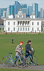 © Licensed to London News Pictures 23/02/2021.        Greenwich, UK. Two friends walk and talk while pushing their bikes in the park. People get out of their homes from a third national Coronavirus lockdown to enjoy some permitted exercise in the sunny weather as temperatures start to rise in Greenwich Park, London. Photo credit:Grant Falvey/LNP
