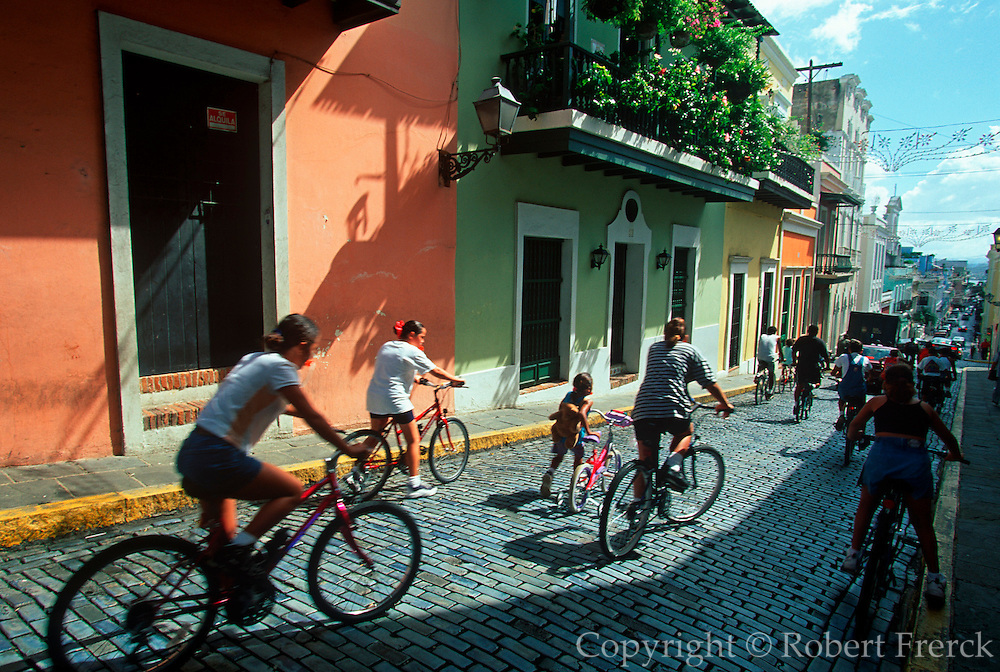 PUERTO RICO, SAN JUAN World Heritage Site, balconied two storied buildings along Calle Christo in the heart of the old city; bicycle race