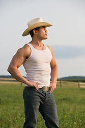 profile of a cowboy in a tank top outdoors on a ranch