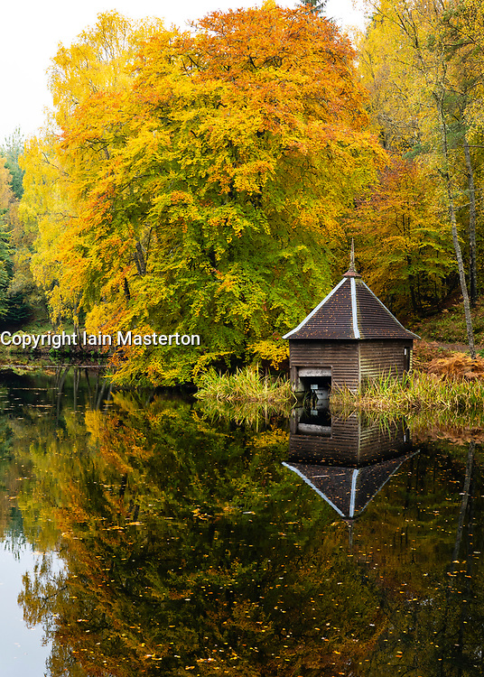 Autumn colours on woodland foliage and wooden boathouse at Loch Dunmore in Faskally Wood near Pitlochry in Perthshire, Scotland,UK