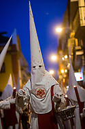 A nazareno passing through the procession. His robe is spotted by drops of hot, red wax dripping from the candles of the attendants. Seville, Spain.
