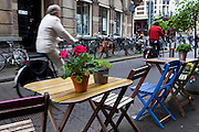Cyclists pass a cafe in The Hague