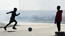 SOUTH AFRICA - South Africa - Cape Town - 28 July 2020 - Children in Mandela Park in Khayelitsha playing soccer on the Joe Gqabi road while others were part of the land invasion on the field right next to the same road.The government announced the closure of schools for four weeks in trying to combat the spread of the Coronaviru known as Covid-19. Picture: Phando Jikelo/African News Agency(ANA)