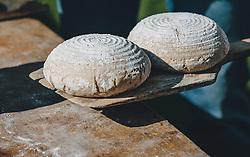 THEMENBILD - Bauernbrotlaibe vor dem Backen auf einem Holzbrett. Ein Bäcker bäckt wöchentlich Bauernbrot und Milchbrot bzw. Osterstriezel, im alten, traditionellen Holzofen neben dem Meixnerhaus am Kirchbichl oberhalb von Kaprun, aufgenommen am 10. April 2020 in Kaprun, Oesterreich // Farmhouse bread loaves before baking on a wooden board. A baker bakes farmhouse bread and milk bread or Osterstriezel every week, in the old, traditional wood-burning oven next to the Meixnerhaus at the Kirchbichl above Kaprun in Kaprun, Austria on 2020/04/10. EXPA Pictures © 2020, PhotoCredit: EXPA/Stefanie Oberhauser