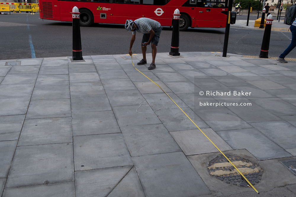 Sizing up proportions and pavement width, a man stretches a measuring tape at Bank in the City of London, in order to measure the possibility of placing tables there for a nearby bar, as part of social distancing measures, on 21st August 2020, in London, England.