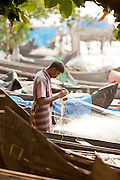 A fisherman untangles a net on the shore at Cochin, Kerala, India