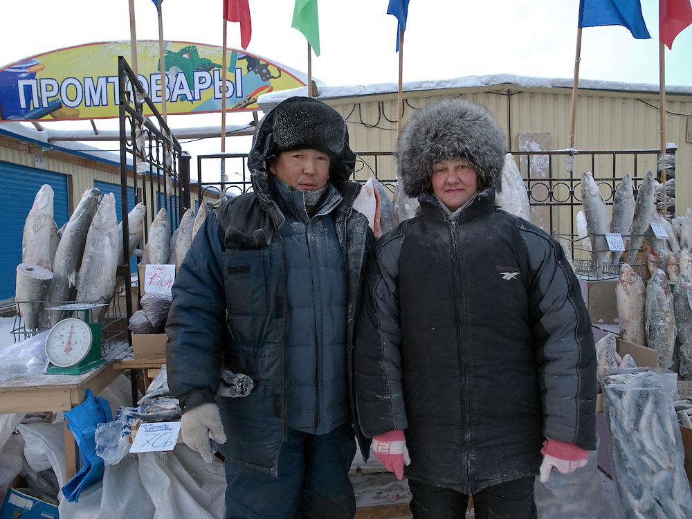 Verkaeufer vor ihrem Stand mit tiefgefrorenen Beeren und stehenden Fischen auf dem Freiluft Markt im Zentrum von Jakutsk. Jakutsk hat 236.000 Einwohner (2005) und ist Hauptstadt der Teilrepublik Sacha (auch Jakutien genannt) im Foederationskreis Russisch-Fernost und liegt am Fluss Lena. Jakutsk ist im Winter eine der kaeltesten Grossstaedte weltweit mit durchschnittlichen Winter Temperaturen von -40.9 Grad Celsius. Die Stadt ist nicht weit entfernt von Oimjakon, dem Kaeltepol der bewohnten Gebiete der Erde.<br /> <br /> Sellers in front of their stall with deep frozen berries and standing fishes on the Yakutsk outdoor fish market. Yakutsk is a city in the Russian Far East, located about 4 degrees (450 km) below the Arctic Circle. It is the capital of the Sakha (Yakutia) Republic (formerly the Yakut Autonomous Soviet Socialist Republic), Russia and a major port on the Lena River. Yakutsk is one of the coldest cities on earth, with winter temperatures averaging -40.9 degrees Celsius.