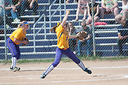 The pitcher for Elmira College is in the middle of her wind up about to deliver the ball to home plate.