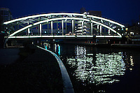 """Mannen Bashi Bridge replaced an ancient wooden arched structure, made famous in a Hokusai woodblock painting, """"Under Mannen Bridge at Fukagawa"""" with its view of Mt Fuji.  The more modern steel structure appears to be neon at night, though it is only reflection onto the metal from the illuminations.  The view of Mt Fuji cannot be seen these days because of tall buildings on the opposite side of the Sumida River."""