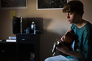 Christian Akridge plays guitar in his room at his home in Wichita Falls, Texas on November 18, 2015.  (Cooper Neill for Rolling Stone)