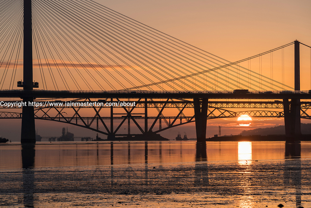 South Queensferry, Scotland, UK. 29 March , 2018. Beautiful sunrise on a clear cold morning behind the three famous bridges crossing the Firth of Forth at South Queensferry. The three bridges are the new Queensferry Crossing, Forth Road Bridge and the iconic Forth (rail) Bridge.