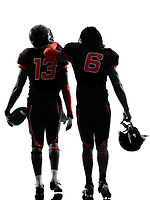 two american football players walking rear view in silhouette shadow on white background