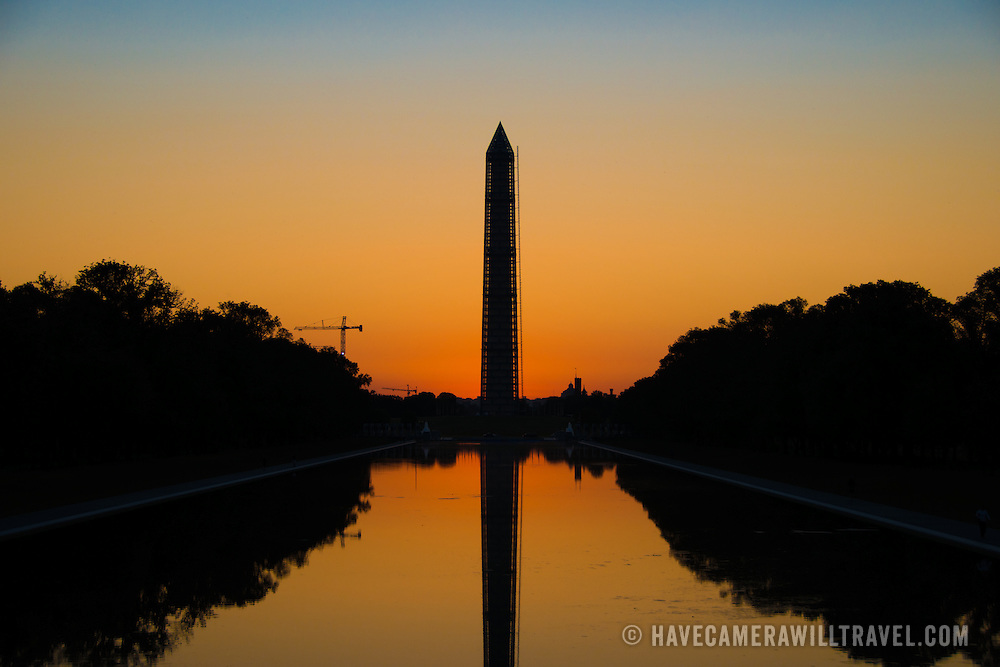 The orange glow in the sky just before dawn behind the Washington Monument and Reflecting Pool in Washington DC.