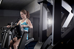 Mid adult woman doing exercise on exercise machine in the gym, Bavaria, Germany
