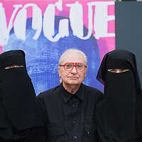 """VENICE, ITALY - JUNE 01:  Cretaor of fashion magazines and artisit Flavio Lucchini poses with two models in front of his work """"poster/vogue"""" part of the exhibition """"What Women Want (?)"""" on June 1, 2011 in Venice, Italy. The exhibition addresses the controversiat theme of the burqa"""