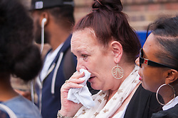 Tottenham, London, August 4th 2015. Family, friends and supporters of alleged gangster Mark Duggan, who was shot and killed by police on 4th August 2011 in Tottenham, commemorate his death which led to widespread uprisings and riots, by marching from Broadwater Farm estate to Tottenham police station. His family is demanding a public inquiry into the role of Operation Trident, set up to fight gun and knife crime amongst the black community, whose officers they accuse of putting guns out on the streets of London. PICTURED: An emotional Pamela Duggan, mother of Mark Duggan sheds tears for her lost son, four years after his death.  // Contact: paul@pauldaveycreative.co.uk Mobile 07966 016 296