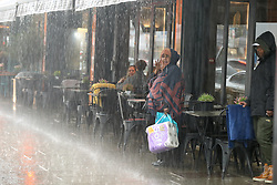 © Licensed to London News Pictures. 17/05/2021. London, UK. People dine outside during heavy rain in north London. More rain is forecast for the South East of England this week. Photo credit: Dinendra Haria/LNP