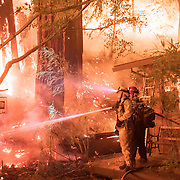 Firefighters work to protect a house near Highway 236 as the CZU Lightning Complex fire rages near Boulder Creek, Calif. on Aug. 20, 2020. Firefighters had to leave the area later, because conditions were too unsafe and the home was destroyed in the fire.