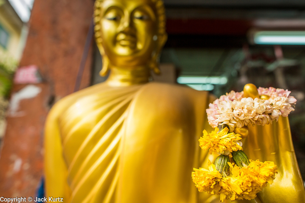 """12 NOVEMBER 2012 - BANGKOK, THAILAND:  A flower garland in the Buddha's hand in front of a shop on Bamrung Muang Street in Bangkok. Thanon Bamrung Muang (Thanon is Thai for Road or Street) is Bangkok's """"Street of Many Buddhas."""" Like many ancient cities, Bangkok was once a city of artisan's neighborhoods and Bamrung Muang Road, near Bangkok's present day city hall, was once the street where all the country's Buddha statues were made. Now they made in factories on the edge of Bangkok, but Bamrung Muang Road is still where the statues are sold. Once an elephant trail, it was one of the first streets paved in Bangkok. It is the largest center of Buddhist supplies in Thailand. Not just statues but also monk's robes, candles, alms bowls, and pre-configured alms baskets are for sale along both sides of the street.    PHOTO BY JACK KURTZ"""