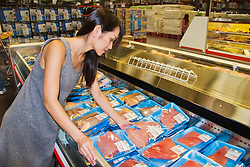 woman shopper choosing neatly packaged fresh fillet steaks of Pacific Ocean blue marlin meat for sale at supermarket in Kailua Kona, Big Island of Hawaii, Makaira nigricans, imported from F.S.M. - Federated States of Micronesia