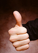 Close up, wide angle view of businessman's hand making thumbs up with glowing brown background