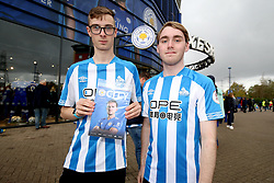 Huddersfield Town fans hold up a match programme outside the stadium prior to the Premier League match at the King Power Stadium, Leicester.