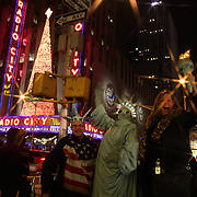 Tourists pose with a Statue of Liberty street busker at Christmas time on 6th Avenue, Manhattan, New York USA. 25th November 2012. Photo Tim Clayton