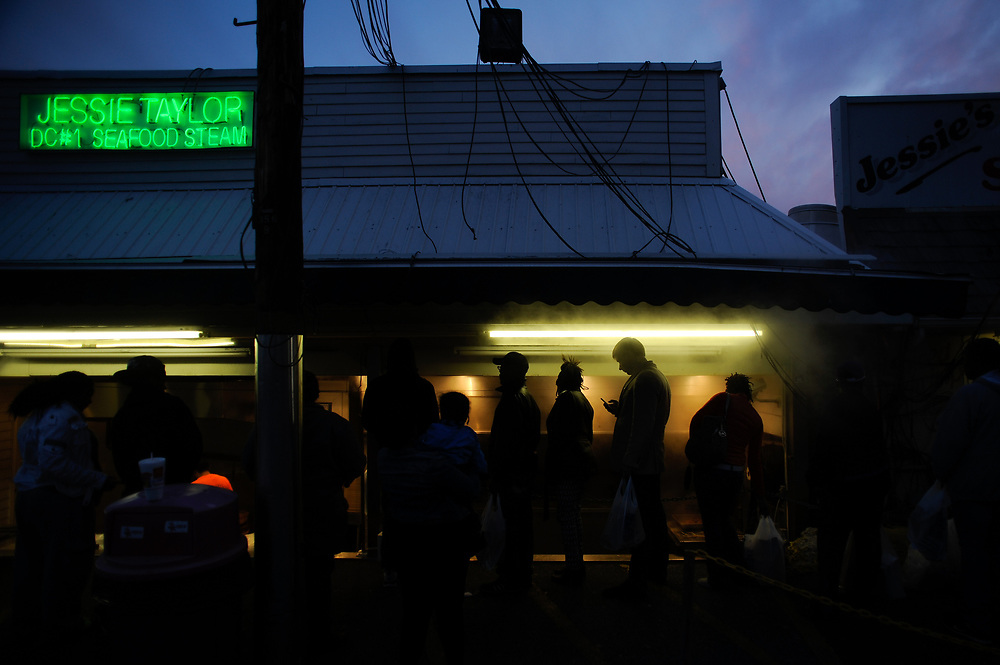 A line of hungry shoppers are shrouded in steam outside of Jessie Taylor at the Maine Ave. Fish Market along Fisherman's Wharf just after sunset in Washington, D.C.