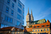 Late afternoon sun hits the cathedral of Zagreb with the modern designed government office building in the foreground.