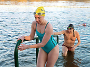 Members of the Serpentine Swimming Club walks climb out of the Serpentine Lake after a Saturday race on a cold Winter's day, Hyde Park, London, UK. The Serpentine Lake is situated in Hyde Park, London's largest central open space. The Serpentine Swimming Club was formed in 1864 'to promote the healthful habit of bathing in open water throughout the year'.  Its headquarters were beneath an old elm tree on the south side of the lake, a wooden bench for clothing being the only facility.  At this time London was undergoing rapid expansion and Hyde Park was now in the centre of a densely populated built up area and provided a place of relaxation to its urbanised masses. Now, the club has its own (somewhat spartan) changing facilities and members are  permitted by the Royal Parks to swim in the lake any morning before 09:30.  They race every Saturday morning throughout the year, regardless of the weather.