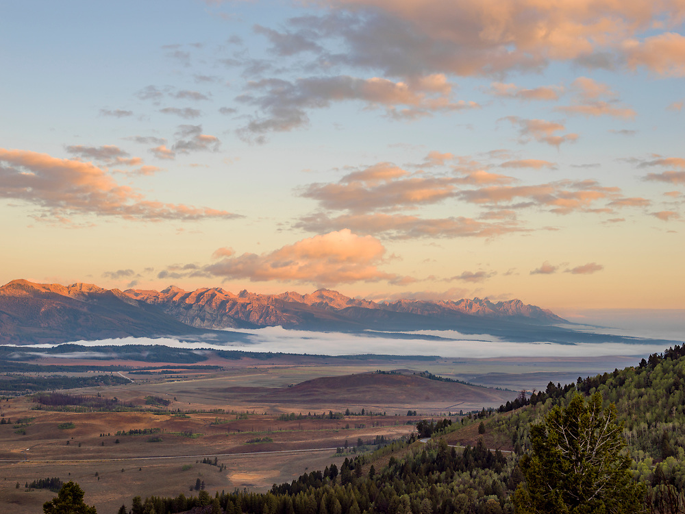 Sunrise golden clouds in the Sawtooth Valley in early morning light with the Sawtooth Mountain Range near Stanley Idaho. Licensing and Open Edition Prints.