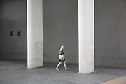 Woman walking past two concrete columns, part of the architecture of the Royal Festival Hall on the Southbank, London, United Kingdom. The South Bank is a significant arts and entertainment district, and home to an endless list of activities for Londoners, visitors and tourists alike. (photo by Mike Kemp/In Pictures via Getty Images)