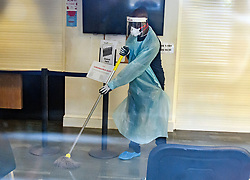 © Licensed to London News Pictures. 13/02/2020. London, UK. A man in a medical mask cleaning surfaces inside Ritchie Street Health Centre in Islington which has closed due to the Coronavirus COVID-19 outbreak, according to a notice on its website. Photo credit: Ben Cawthra/LNP