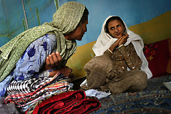 Mukhtar Mai, and Ikbal Mai, talk inside her home, Meerwala, Pakistan, April 28, 2005. Mai, 33, went against the Pakistani tradition of committing suicide when she brought charges against the men who gang raped her nearly three years ago. With money from the ruling she opened two schools, one for girls, the other for boys. Mai cited that education is the only thing that will stop such acts from happening. Ikbal Mai, is the mother of Shanza Sehr, who is a teacher at the girls school.