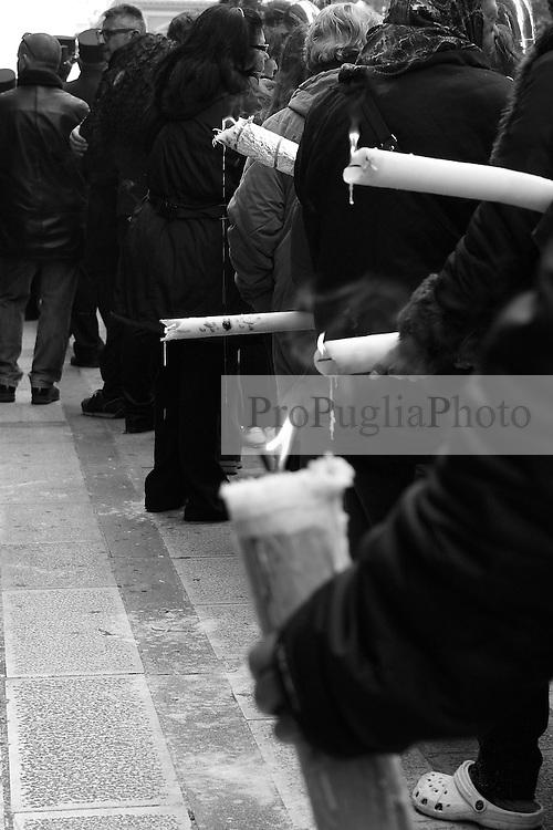 I riti della Settimana Santa a Taranto, fedeli seguono la processione portando ceri.