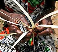Kigali, Rwanda -A woman's fingers work at plating grass as she weaves a mat in a rural area outside of Kigali, Rwanda.