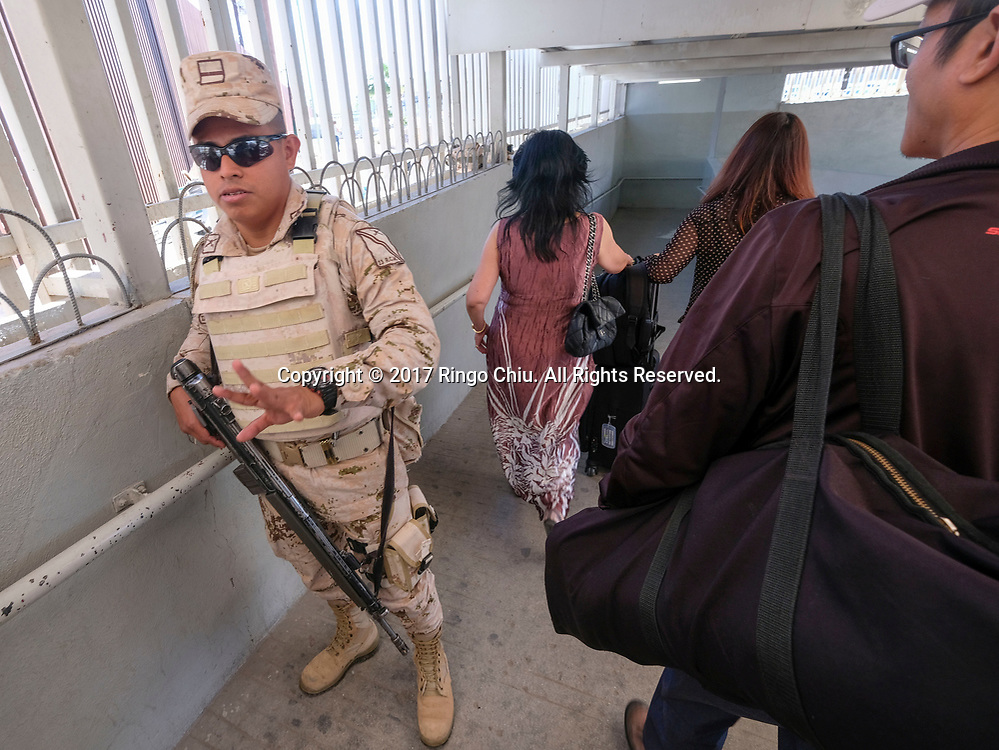 A Mexican border police officer stand guards as people enter the Mexico from Calexico, California on Wednesday April 19, 2017. (Xinhua/Zhao Hanrong)(Photo by Ringo Chiu/PHOTOFORMULA.com)<br /> <br /> Usage Notes: This content is intended for editorial use only. For other uses, additional clearances may be required.