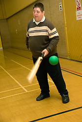 Day service user with limited mobility catching a ball with one hand during an indoor cricket game in the gym,