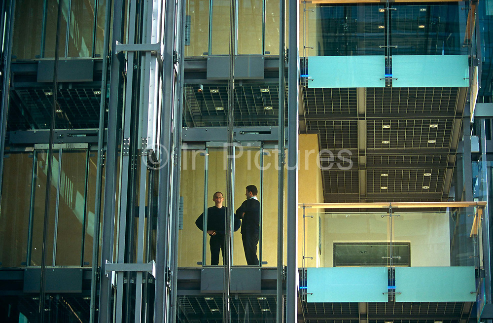 Employees of the former US giant ENRO corporation at the London offices in March 2000, stand at the doors to a lift (elevator) amid glass and polished steel. We are looking up at them from the ground floor as they wait for the lift to bring them down the building's atrium. This is in the months before the company's subsequent collapse with the loss of 22,000 people worldwide. Enron Corporation was an American energy company based in Houston, Texas. Before its bankruptcy in 2001, Enron was one of the world's leading electricity, natural gas, pulp and paper, and communications companies, with claimed revenues of nearly $101 billion in 2000. Oblivious to their employer's troubles, the two men seem relaxed in this workplace which allowed them to work in casually dress, rather than in formal suits, an apparent hallmark of the company's lax work ethic.