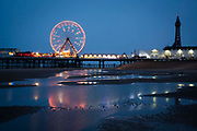 The Blackpool Big Wheel lit-up at dusk on Central Pier, Blackpool, Lancashire, England, United Kingdom.  Designed by John Isaac Mawson and opened in 1868, of the three piers, the Central Pier's emphasis is on fun. The lights from the pier reflect in the sea water on the beach.