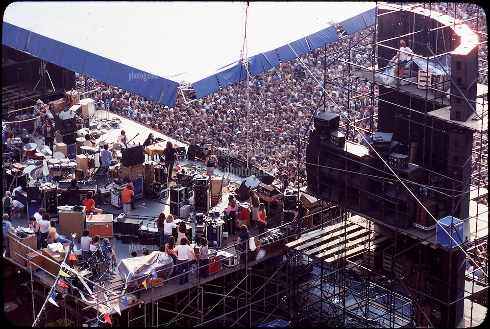 The Grateful Dead Live at Giants Stadium September 2, 1978. The Band on Stage performing. Photo taken behind the Stage also showing the right PA Stack.